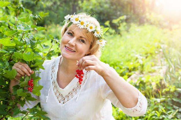 Kobieta w ogrodzie, zbierz czerwone jagody. uśmiecha się kobieta w średnim wieku. pokazuje owoce.