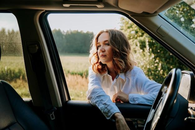 Kobieta w oknie samochodu. wycieczki i wyjazdy poza miasto. koncepcja podróży i radości