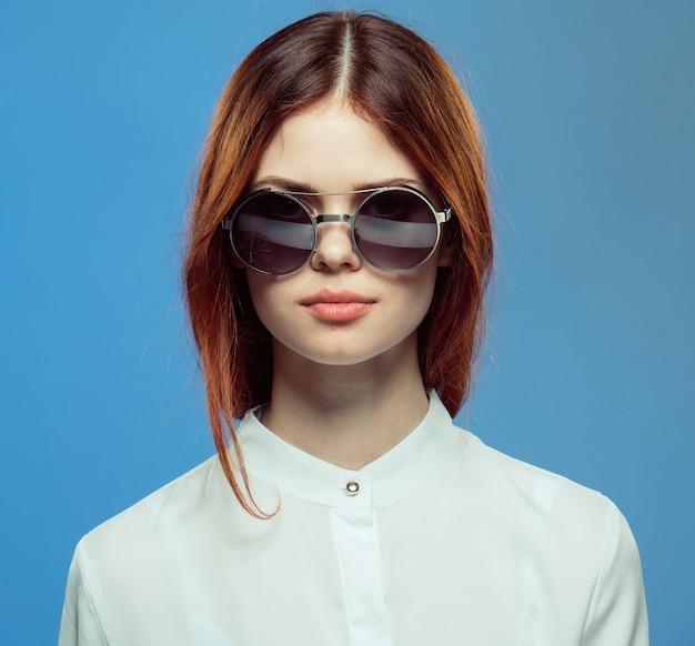 Kobieta w okrągłych okularach przeciwsłonecznych i białej koszuli