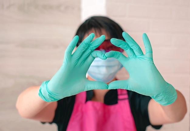 Kobieta w okularach fartuch gumowe rękawiczki pokazujące znak miłości palcami zdrowie opieka zdrowotna