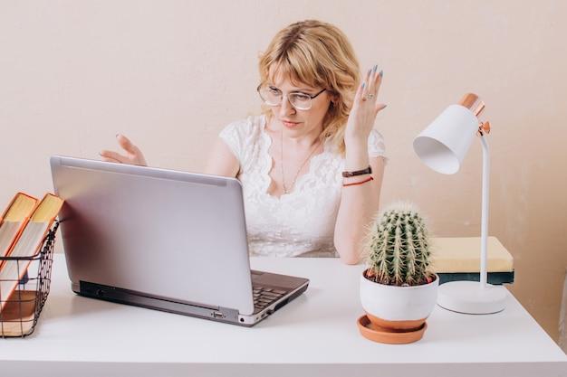 Kobieta w okularach i białej bluzce pracuje przy laptopie i ze zdziwieniem patrzy na monitor