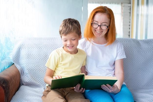 Kobieta w okularach i chłopiec rasy kaukaskiej siedzą na kanapie i czytają książkę, śmiejąc się i bawiąc