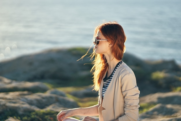 Kobieta w okularach i swetrze w górach w pobliżu morza na krajobrazie przyrody