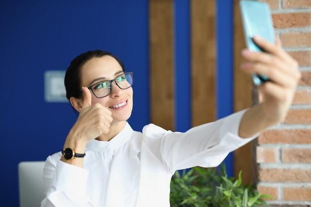 Kobieta w okularach jest fotografowana na telefonie i pokazuje kciuk w górę