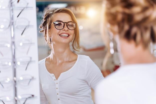 Kobieta w okularach patrzy w lustro. sklep z okularami. kobieta w sklepie optycznym. sklep okulistyczny. zbliżenie.