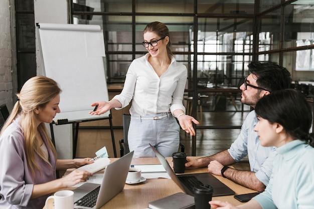 Kobieta w okularach podczas profesjonalnego spotkania z kolegami z zespołu