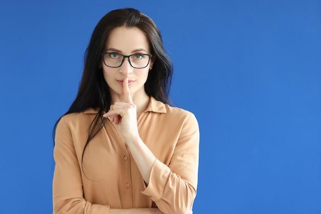 Kobieta w okularach pokazuje palec wskazujący w pobliżu ust