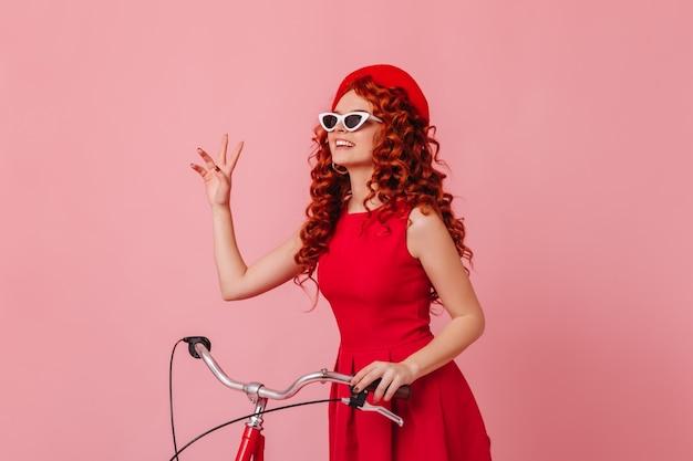 Kobieta w okularach przeciwsłonecznych i czerwonym berecie macha pozdrowieniami i trzyma kierownicę na różowej przestrzeni.