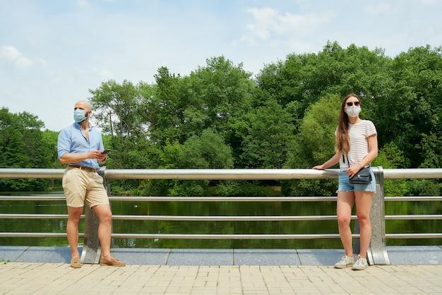 Kobieta w okularach przeciwsłonecznych i mężczyzna trzymający odległość kilku metrów, aby uniknąć rozprzestrzeniania się koronawirusa w pobliżu rzeki.