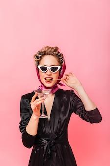 Kobieta w okularach przeciwsłonecznych i szaliku gryzie oliwkę i trzyma martini