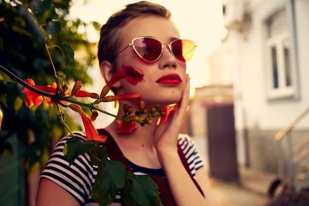 Kobieta w okularach przeciwsłonecznych na ulicy w pobliżu kwiatów pozuje styl życia