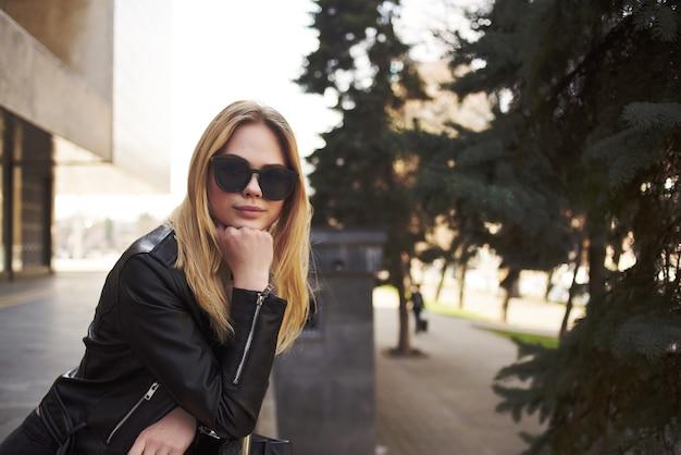 Kobieta w okularach przeciwsłonecznych na zewnątrz w pobliżu budynku spacer moda glamour