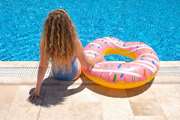 Kobieta w okularach przeciwsłonecznych nadmuchiwany pączek w pobliżu basenu w ośrodku.