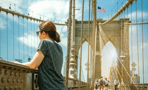 Kobieta w okularach przeciwsłonecznych patrząca na panoramę miasta z mostu brooklińskiego z panoramą manhattanu w tle, w nowym jorku