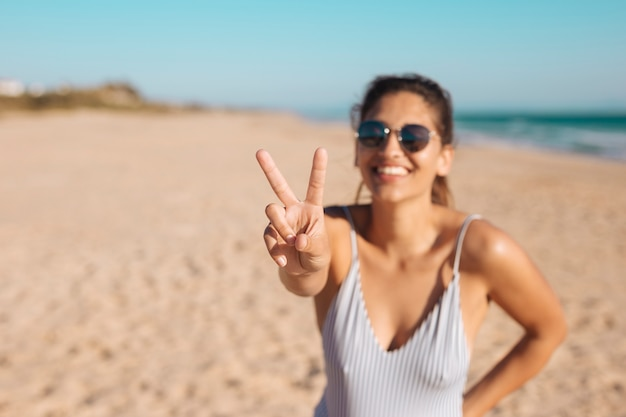 Kobieta w okularach przeciwsłonecznych robi v westchnieniu