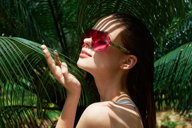 Kobieta w okularach przeciwsłonecznych stroje kąpielowe zielone liście egzotyczne słońce