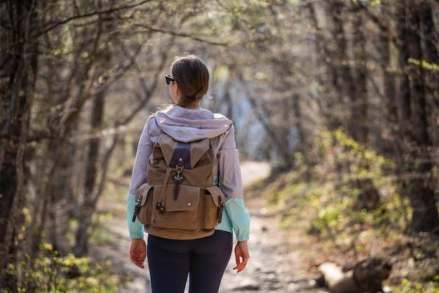 Kobieta w okularach przeciwsłonecznych z dużym plecakiem stoi na leśnej ścieżce i rozgląda się. wędruj sam. szukaj przygody.