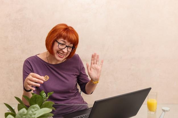 Kobieta w okularach przy laptopie po pracy rozmawia z koleżanką o koronawirusie