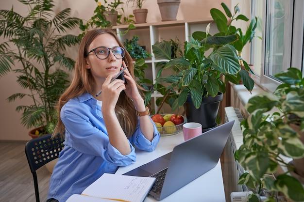 Kobieta w okularach rozmawia przez telefon podczas nauki w domu online