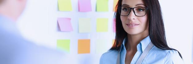 Kobieta w okularach stoi obok białej tablicy naprzeciwko kolegi. komunikacja partnerów na temat koncepcji forów biznesowych
