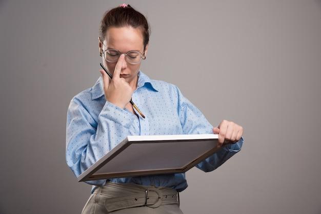 Kobieta w okularach, trzymając płótno i pędzel na szarym tle. wysokiej jakości zdjęcie