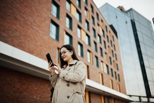 Kobieta w okularach używa smartfona.