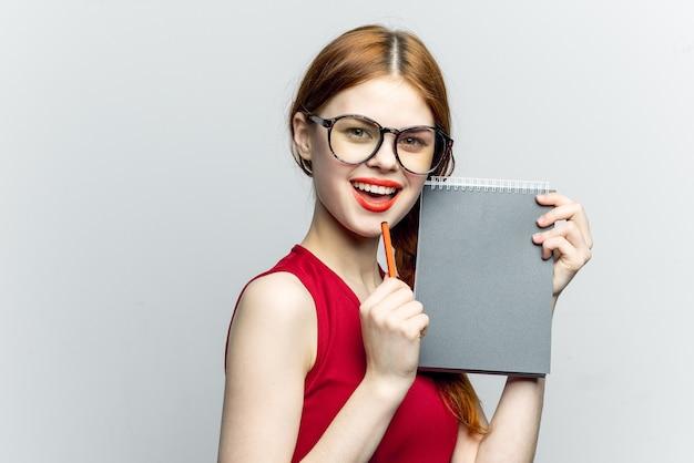 Kobieta w okularach z notatnikiem i piórem, student
