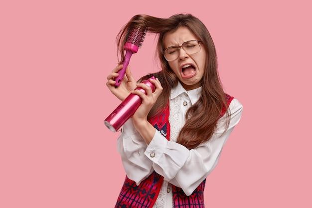 Kobieta w panice ma problematyczne włosy, nie może szczotkować, ma przygnębiony wyraz twarzy, trzyma szczotkę do włosów i lakier do włosów, spóźniona, ubrana w stare modne ciuchy, odizolowana na różowej ścianie