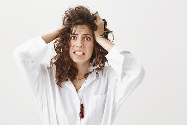 Kobieta w panice rzuca włosy i patrzy przestraszona
