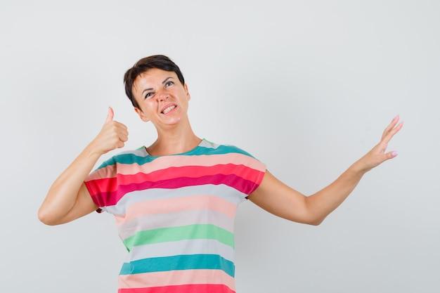 Kobieta w pasiastej koszulce pokazuje gest stopu z kciukiem do góry i patrząc niezdecydowany, widok z przodu.
