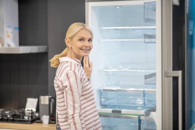 Kobieta w pasiastej koszuli wybiera lodówkę w salonie