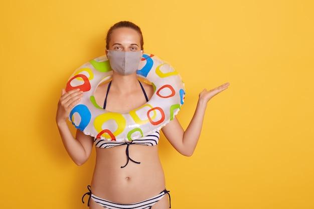 Kobieta w pasiastym kostiumie kąpielowym z gumowym kółkiem na szyi, w higienicznej masce na twarz, odpoczynek i wakacje z covid-19. samica rozkłada dłoń na bok. skopiuj miejsce.