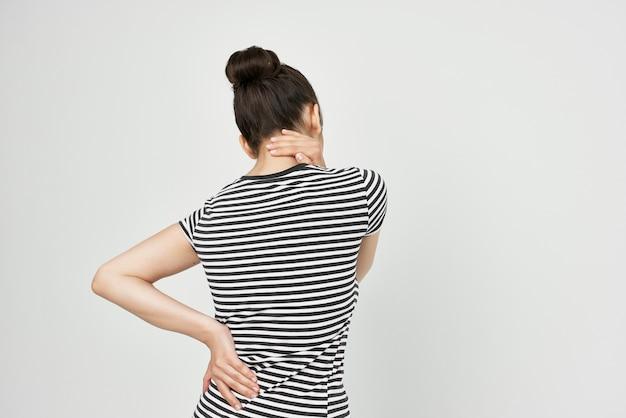 Kobieta w pasiastym tshirt ból pleców dyskomfort niezadowolenie widok z tyłu
