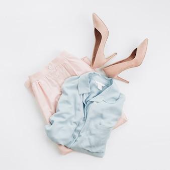 Kobieta w pastelowych ubraniach: dżinsowa koszula, spódnica, buty na obcasie na białej powierzchni