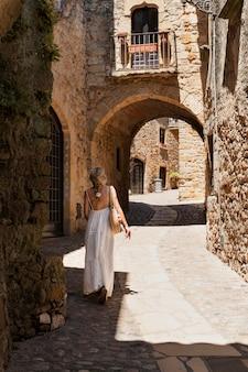 Kobieta w pełnym ujęciu odwiedzająca stare miasto?