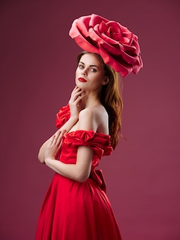 Kobieta w pięknej czerwonej sukience z różą i płatkami róż na czerwonym tle