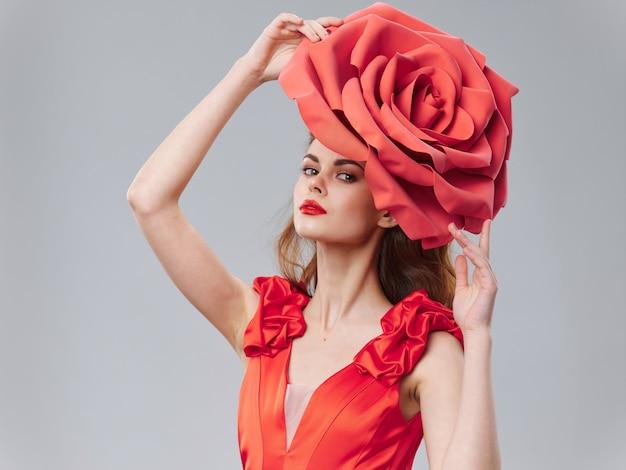 Kobieta w pięknej czerwonej sukience z różą i płatkami róży
