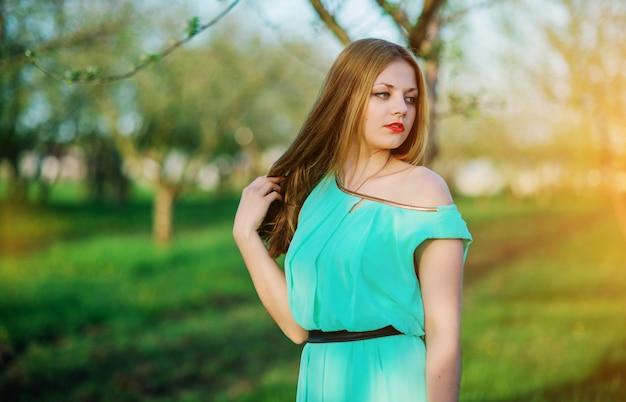 Kobieta w pięknej długiej turkusowej sukni pozuje na łące w ogródzie.