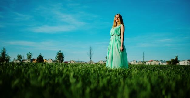 Kobieta w pięknej długiej turkusowej sukni pozuje na łące