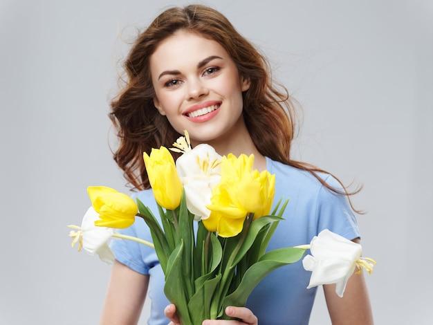 Kobieta w pięknej sukience z kwiatami 8 marca, prezenty kwiaty jasna powierzchnia studio walentynki