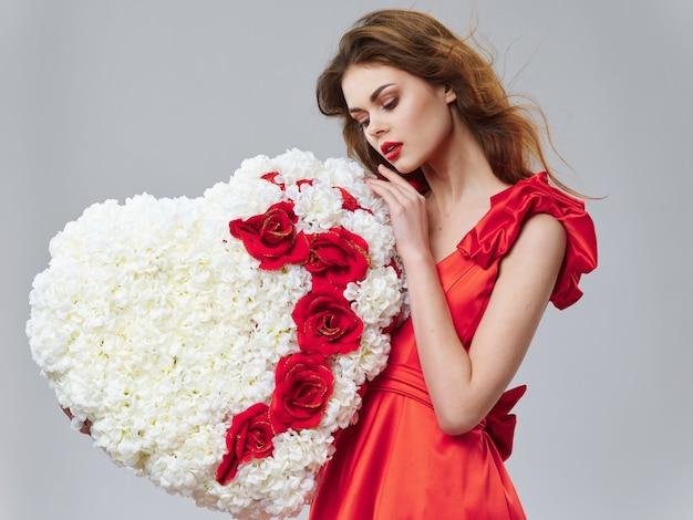Kobieta w pięknej sukni z kwiatami 8 marca, prezenty kwiaty jasnym tle walentynki studio
