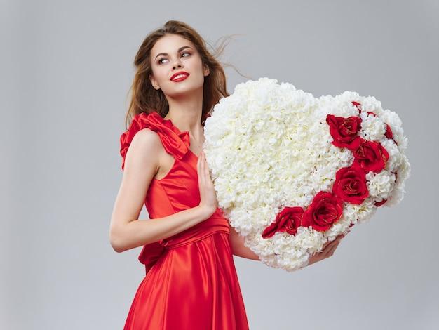 Kobieta w pięknej sukni z kwiatami 8 marca, prezenty kwiaty jasnym tle walentynki