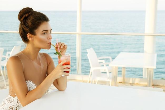 Kobieta w pięknej sukni ze szklanką koktajlu