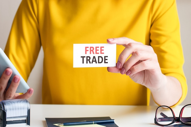 Kobieta w pięknej żółtej sukience siedzi przy biurku i trzyma przed sobą białą kartkę z napisem free trade