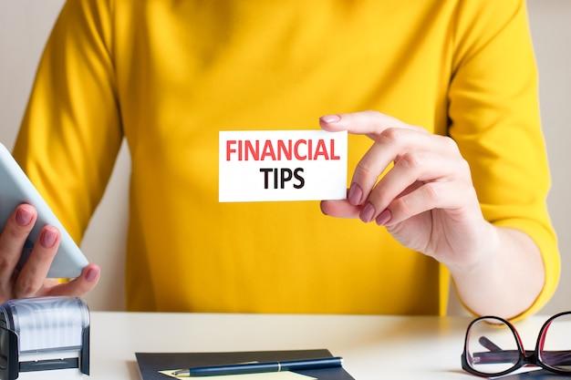 Kobieta w pięknej żółtej sukience trzyma przed sobą białą kartkę z napisem porady finansowe