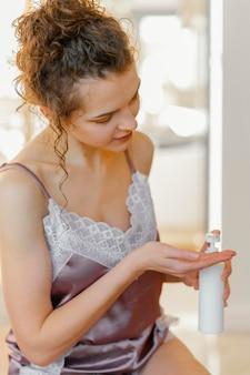 Kobieta w pijamie stosując balsam