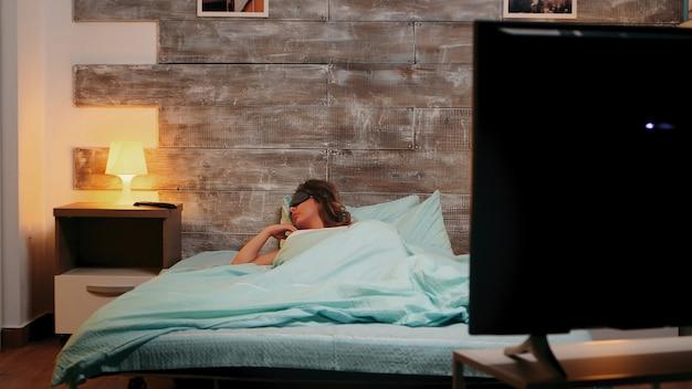 Kobieta w piżamie dużo się rusza podczas snu. kobieta ma koszmar.