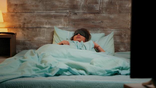 Kobieta w piżamie ma koszmar podczas snu z maską na oczy.