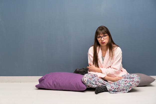 Kobieta w piżamie na podłodze z smutnym i przygnębionym wyrazem twarzy