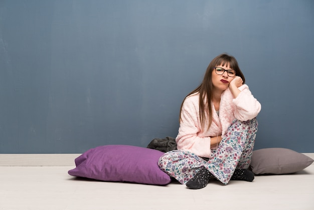 Kobieta w piżamie na podłodze zmartwiona